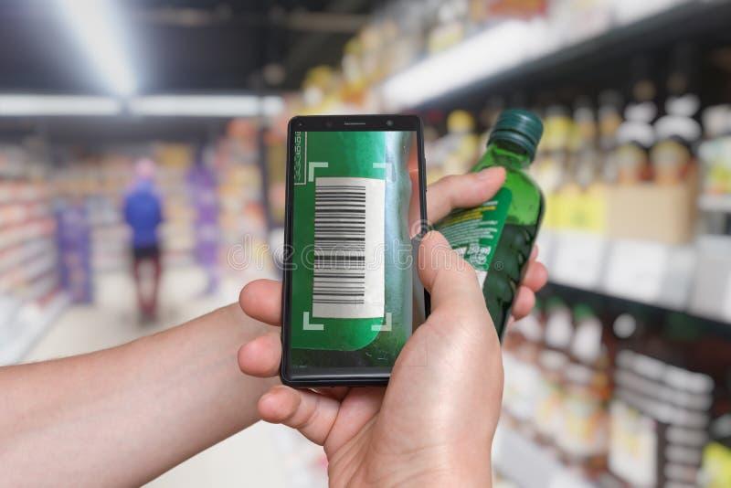 Mannen shoppar i supermarket och avläsande barcode med smartphonen arkivbild