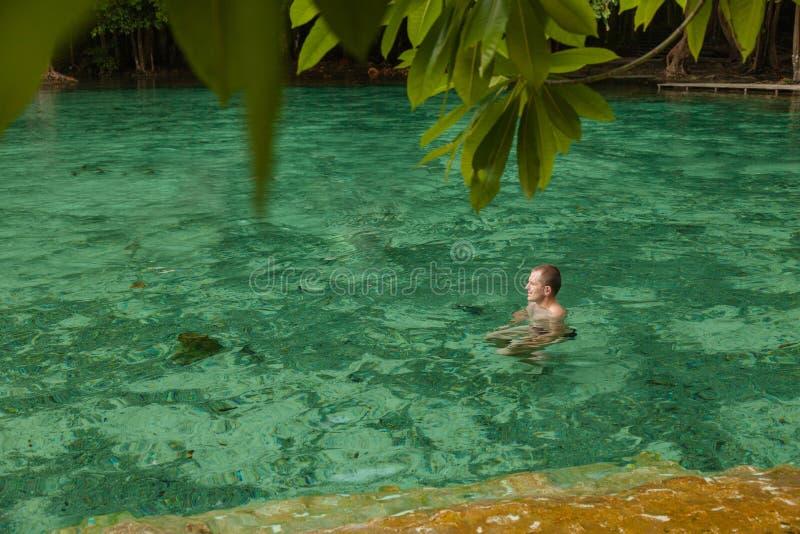 Mannen simmar smaragdpölen THAILAND KRABI arkivfoton