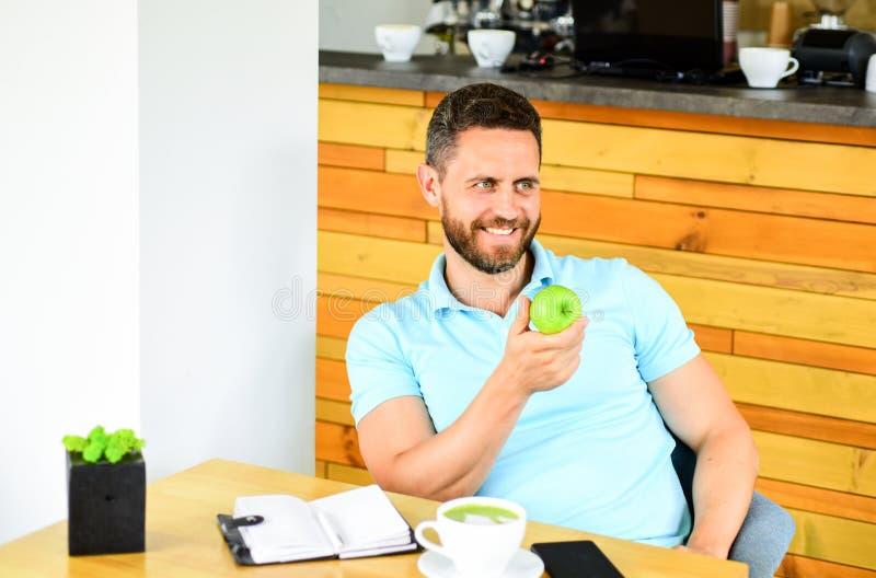 Mannen sitter äter grön äpplefrukt sunt mellanmål Lunch äter äpplet sunda vanor Kaffeavbrott som ska kopplas av Sund manomsorg royaltyfri fotografi