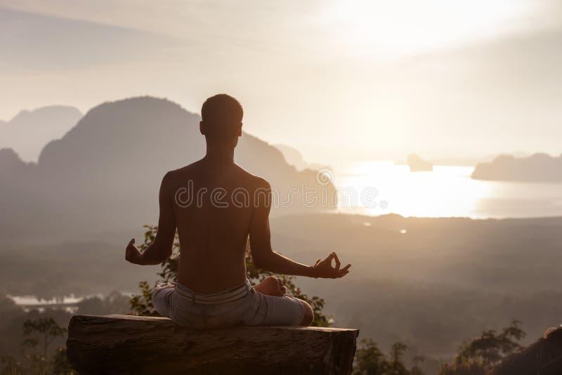 Mannen sitter i yoga poserar på soluppgång mot havet royaltyfri foto