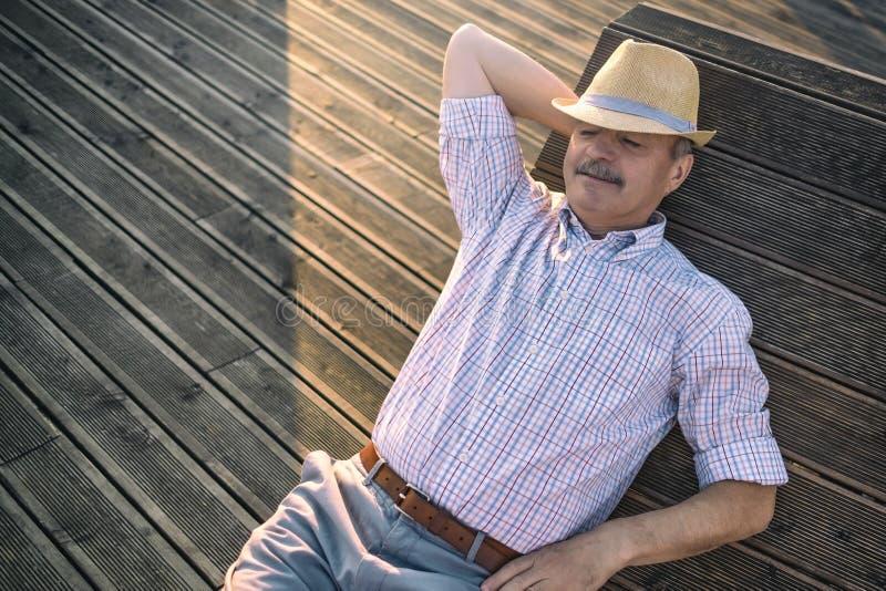 Mannen sitter på bänken som sover tycka om solig dag för sommar arkivfoto