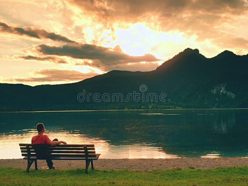 Mannen sitter på bergsjön royaltyfria foton