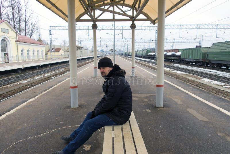 Mannen sitter på en bänk fotografering för bildbyråer