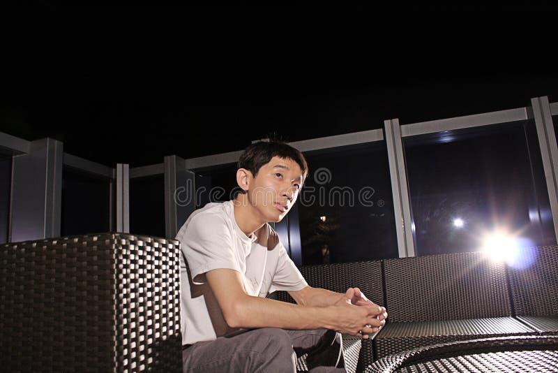 Mannen sitter på en bänk arkivbilder