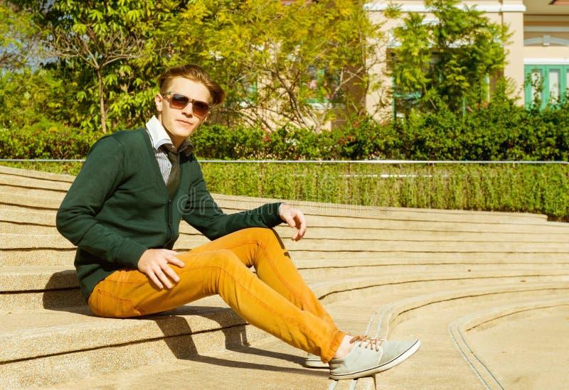 Mannen sitter på gul trappa royaltyfri foto