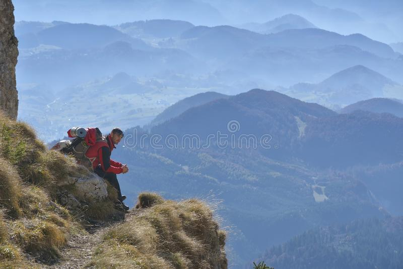 Mannen sitter på maximumet av vaggar och hålla ögonen på in i färgrik mist och dimma i skogdalen arkivbild