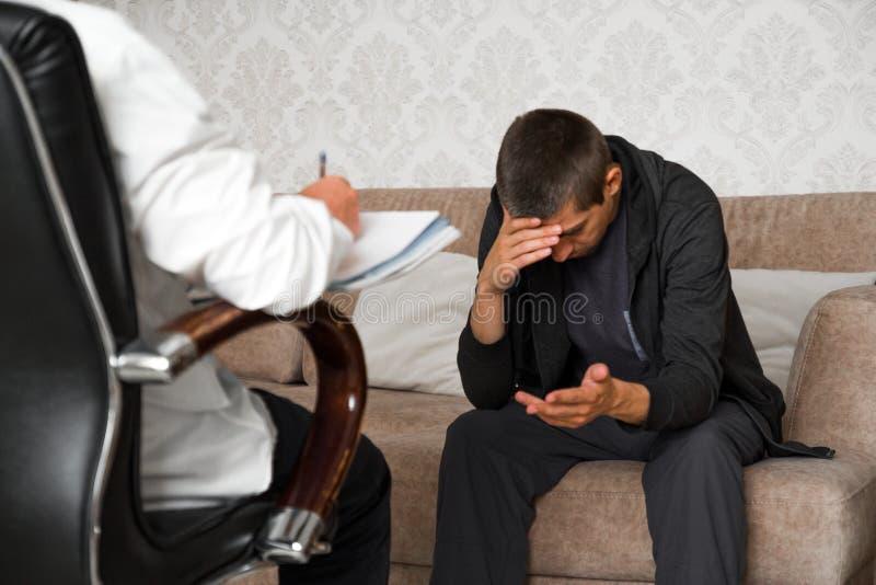 Mannen sitter p? soffan och talar till psykologen, medan doktorn g?r anm?rkningar royaltyfri fotografi