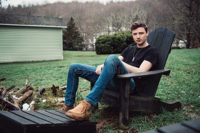 Mannen sitter utomhus på en trästol på trädgården av hans hus på landsbygd royaltyfria bilder
