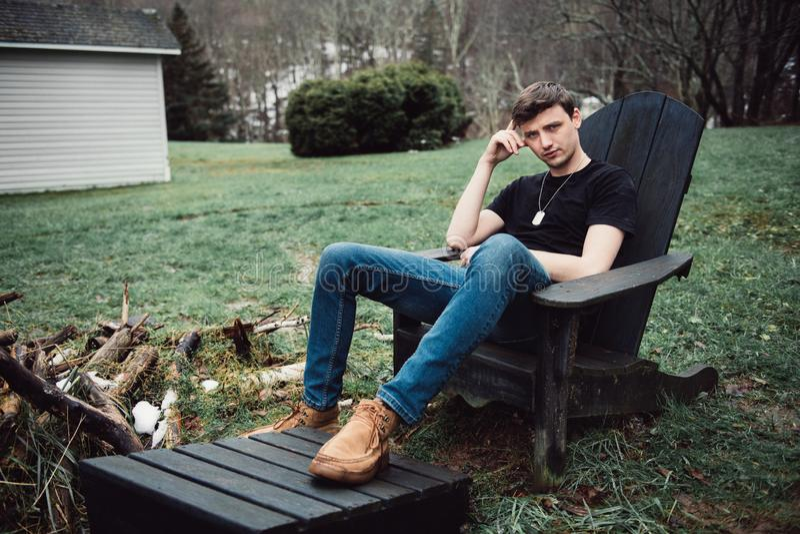 Mannen sitter utomhus på en trästol på trädgården av hans hus på landsbygd royaltyfria foton