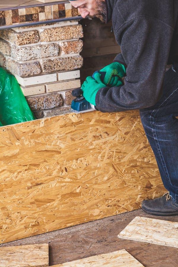 Mannen skrapar den wood plattan med elkraftnivån arkivbild