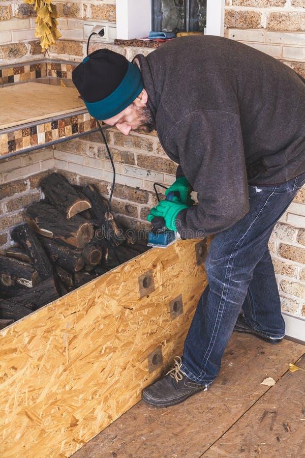 Mannen skrapar den wood plattan med elkraftnivån royaltyfri fotografi
