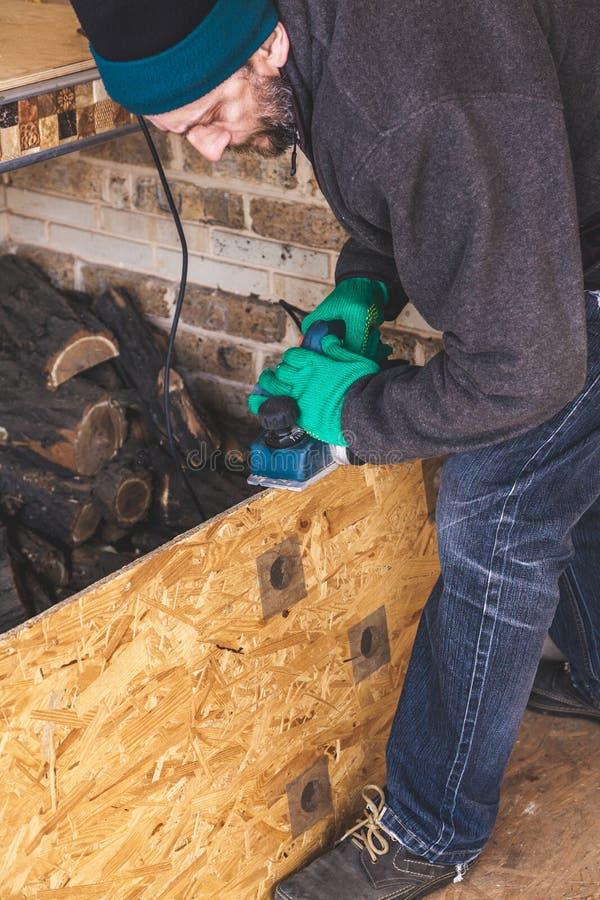 Mannen skrapar den wood plattan med elkraftnivån arkivfoto