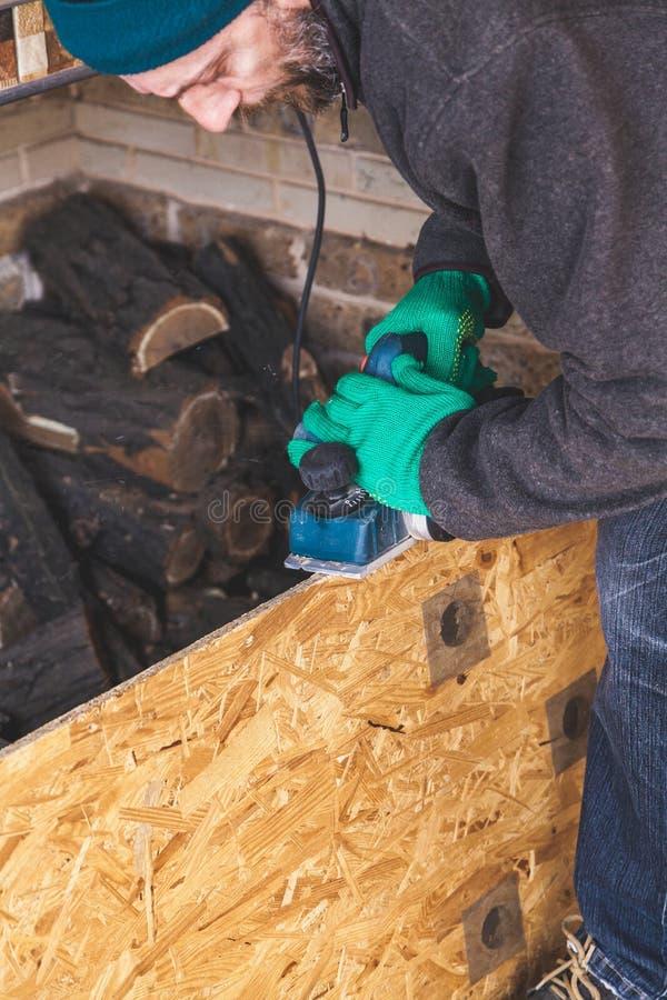 Mannen skrapar den wood plattan med elkraftnivån royaltyfri bild