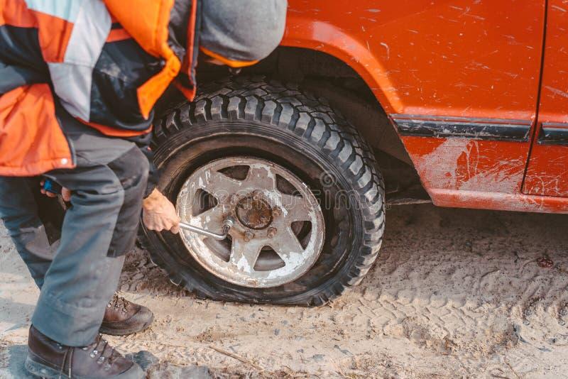 Mannen skruva av bultarna p? hjulet fotografering för bildbyråer