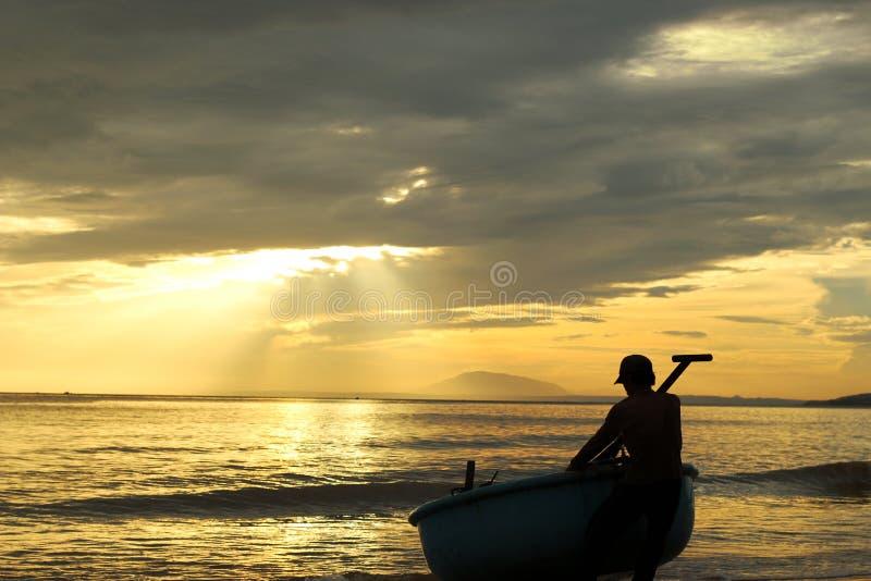 Mannen släpar hans fiskebåt ashore på solnedgången royaltyfri fotografi