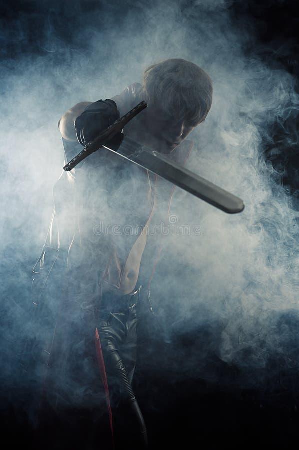 Mannen slogg ett svärd i rök royaltyfria foton
