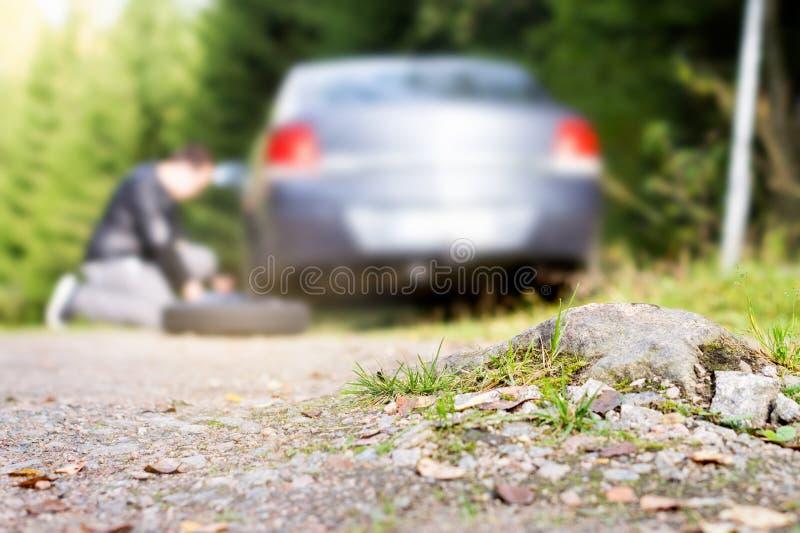Mannen som ändrar det nya extra- hjulet efter medelslag, vaggar på countrysi royaltyfri foto