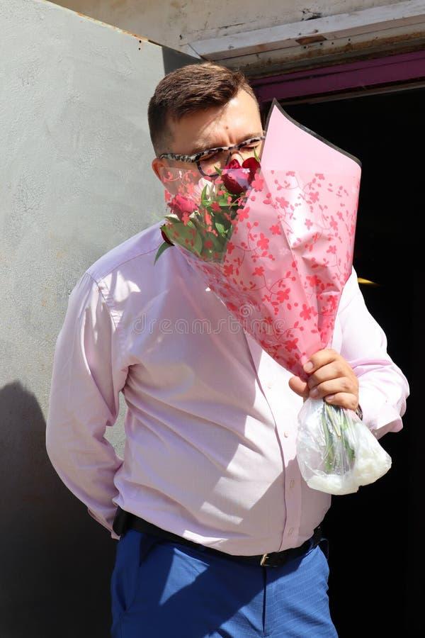 Mannen som är förälskad med en stor bukett av blommor, talar med hans älskling på telefonen royaltyfri fotografi