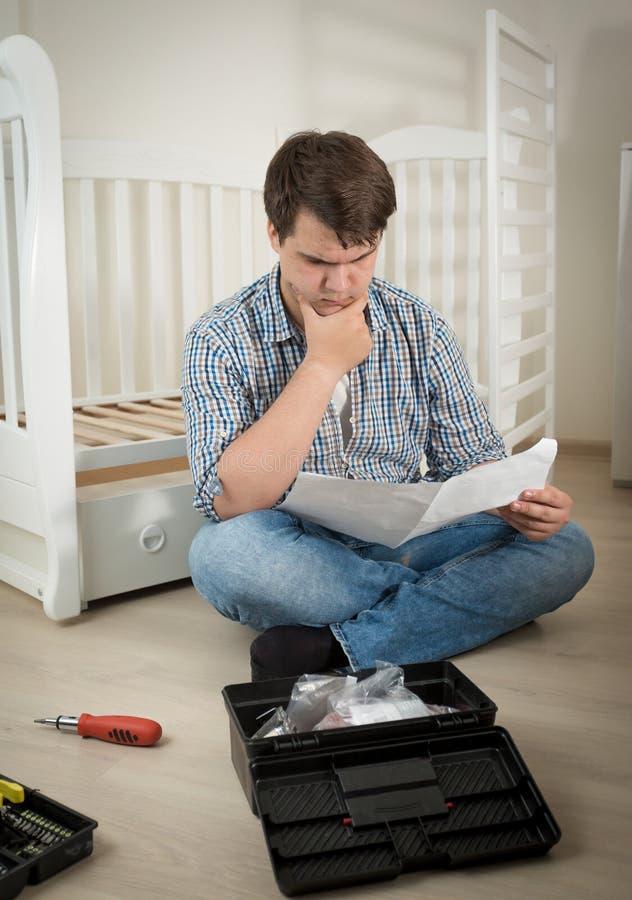 Mannen som är förvirrad om montering, behandla som ett barn säng för ` s royaltyfria bilder