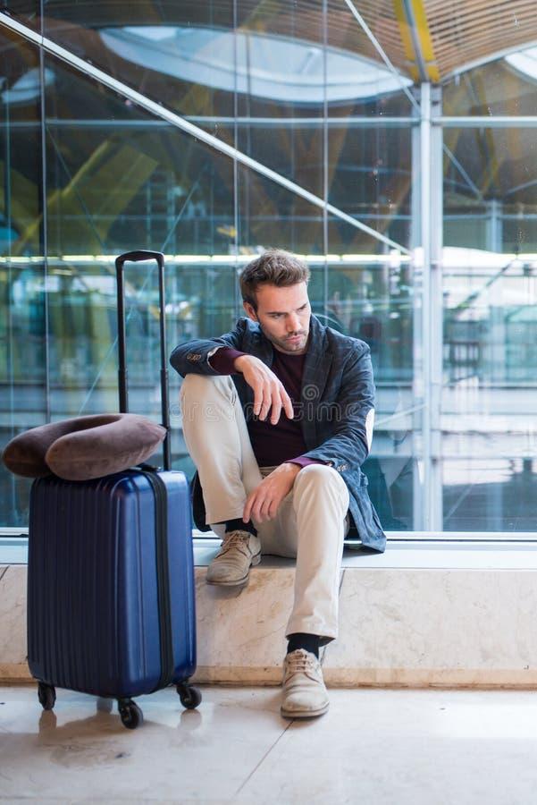 Mannen som är olycklig och som är frustrerad på flygplatsen hans flyg, är cancelle royaltyfria foton