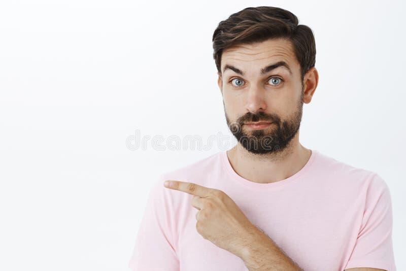 Mannen som antyder finner vi, svar där Stående av den skäggiga grabben som vet något peka som lämnas på att lyfta för kopieringsu royaltyfria foton
