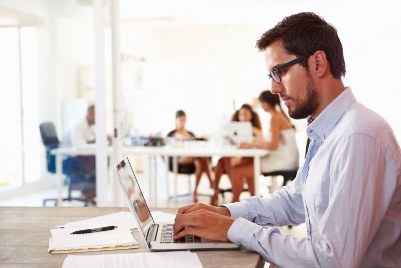 Mannen som använder bärbara datorn i modernt kontor av, startar upp affär royaltyfria foton