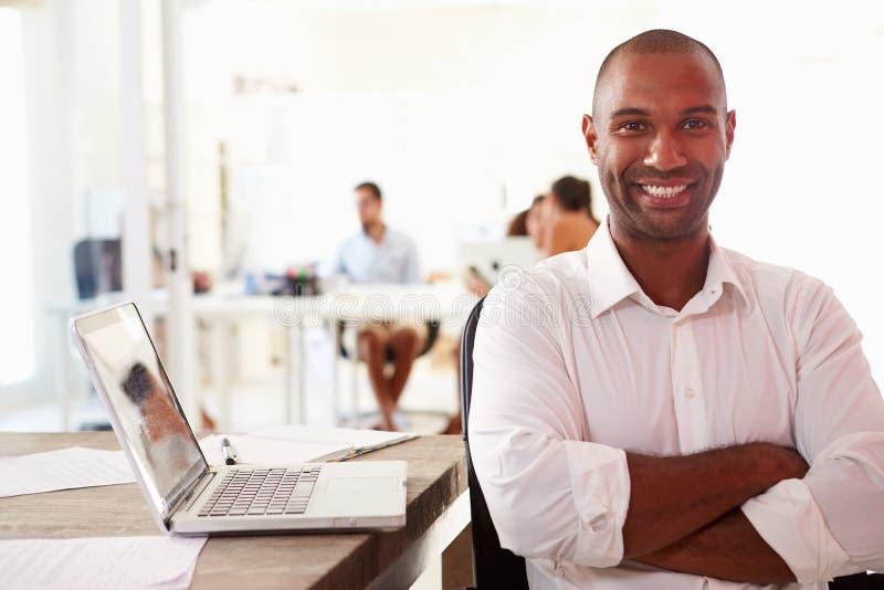 Mannen som använder bärbara datorn i modernt kontor av, startar upp affär arkivbild