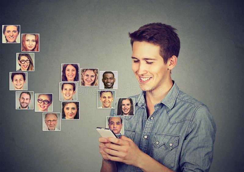 Mannen som använder den smarta telefonen, har många kontakter i mobil phonebook arkivbild