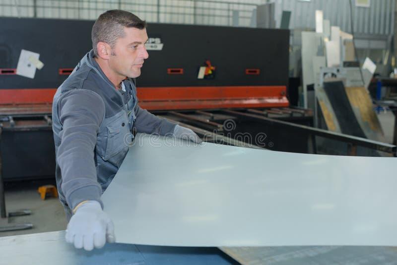 Mannen som arbetar på fabrikstillverkning, blandade klart flöteexponeringsglas royaltyfri foto