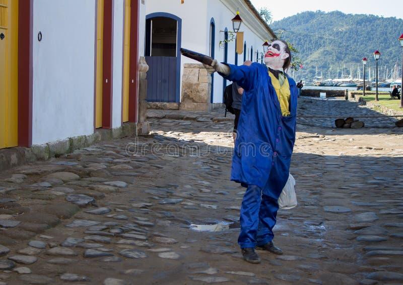 Mannen som bär en blå dräkt, rymmer ett vapen arkivbilder