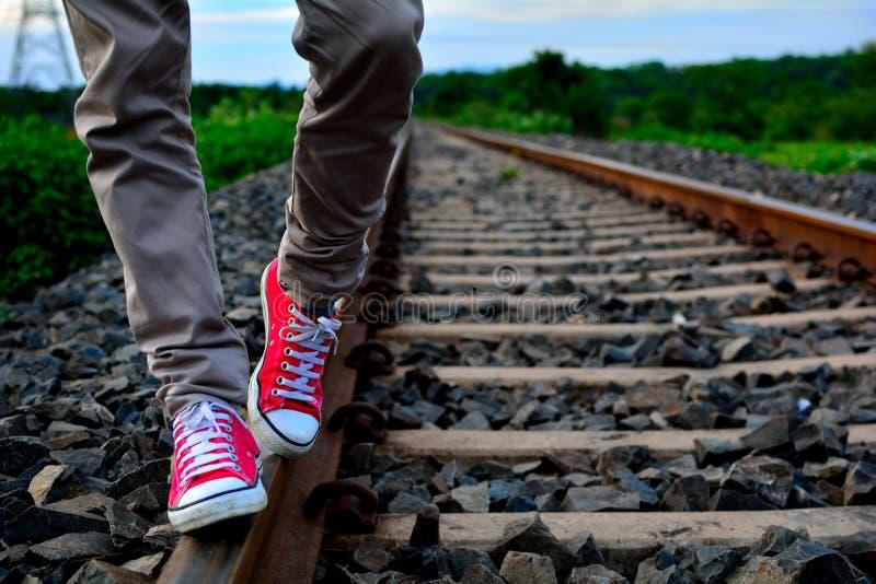 Mannen som bär röda motsatsskor och går på järnvägen, treck royaltyfria bilder