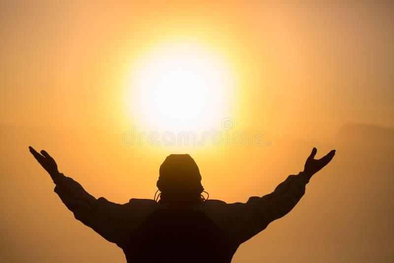 Mannen som ber på solnedgångberg, lyftte händer reser begrepp för andlig avkoppling för livsstil emotionellt, frihet och loppaffä arkivfoton