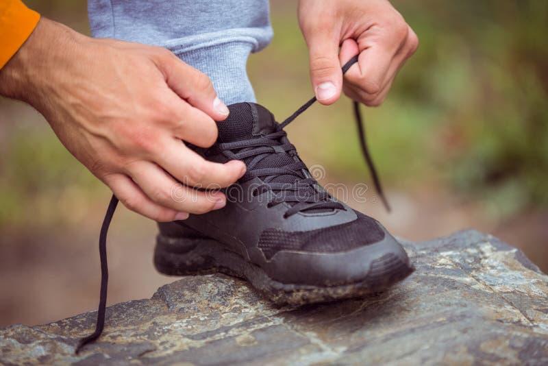 Mannen som binder hans sko, snör åt fotografering för bildbyråer