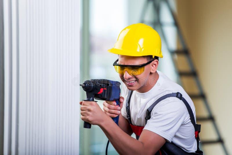 Mannen som borrar väggen med drillborrhålapparaten royaltyfri fotografi