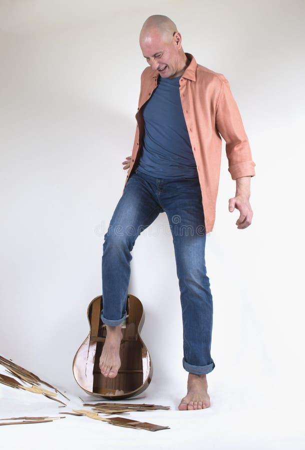 Mannen som bryter gitarren vid hans ben royaltyfria foton