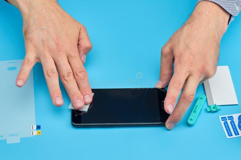 Mannen som byter ut det brutna skärmbeskyddandet för blandat exponeringsglas för smartphone fotografering för bildbyråer