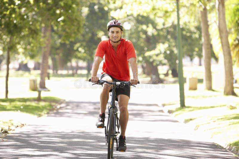 Mannen som cyklar parkerar igenom royaltyfri foto