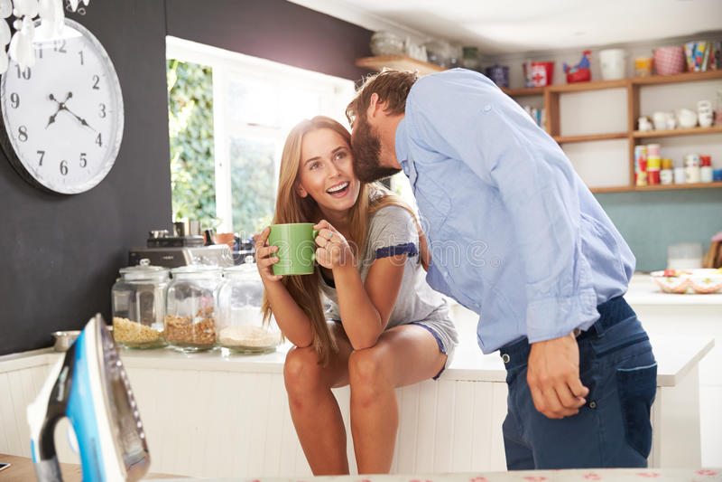Mannen som får klar att lämna för arbete, kysser kvinnan i kök arkivbilder