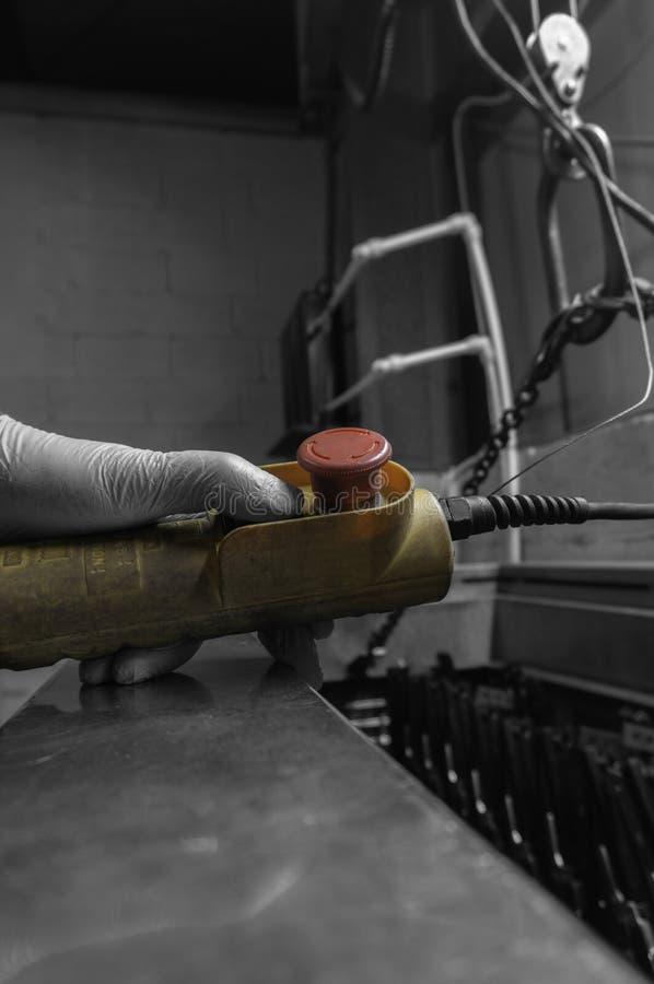 Mannen som fungerar en kontroll för en inomhus kran, hissar i ett fabriksseminarium arkivbild
