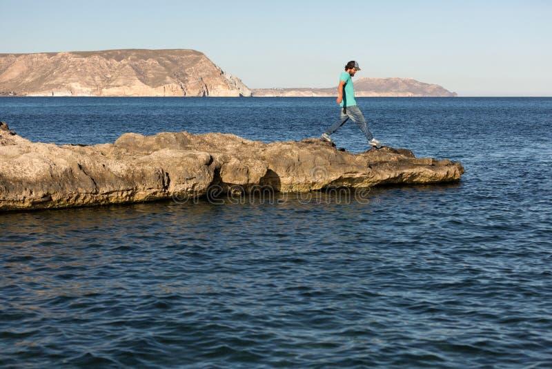Mannen som går på, vaggar bildande mot havet royaltyfria foton