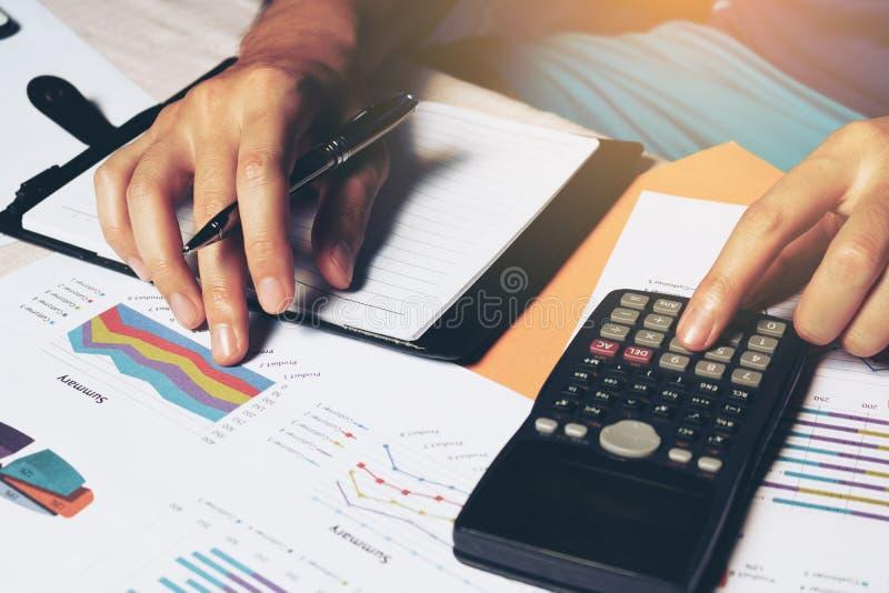 Mannen som gör finans med, beräknar om kostnad på hemmastadd offi för skrivbord fotografering för bildbyråer