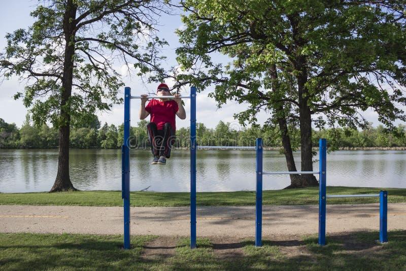 Mannen som gör hakan, ups på en övre stolpe för utomhus- haka arkivfoto