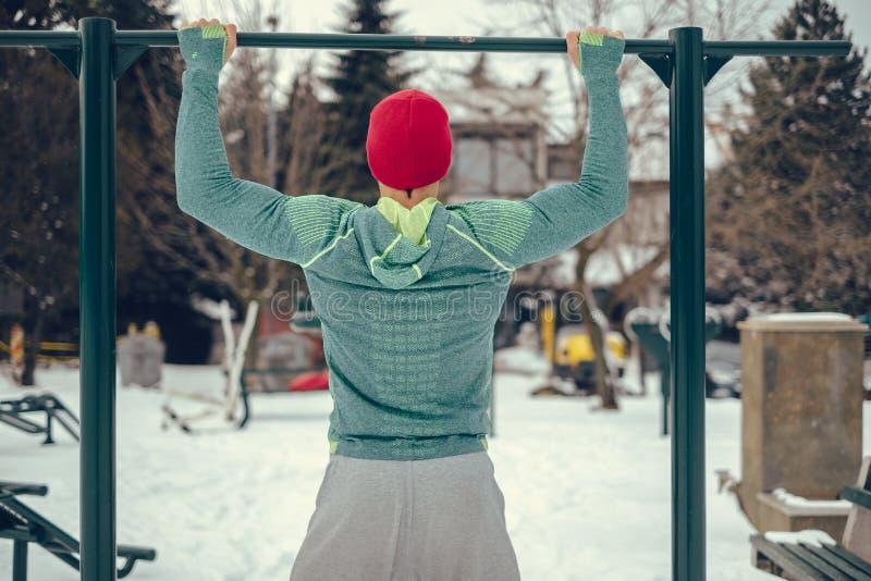 Mannen som gör hakan, ups utanför på en snöig dag arkivbilder