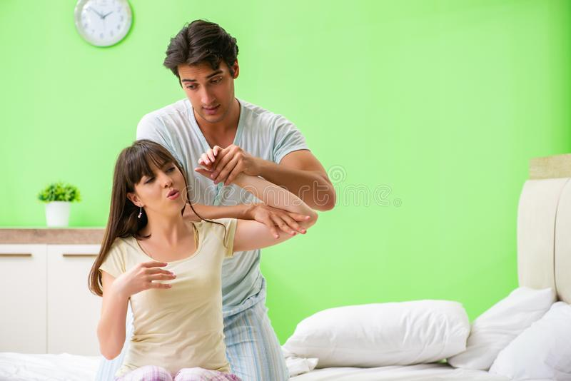Mannen som gör massage till hans fru i sovrum royaltyfri bild