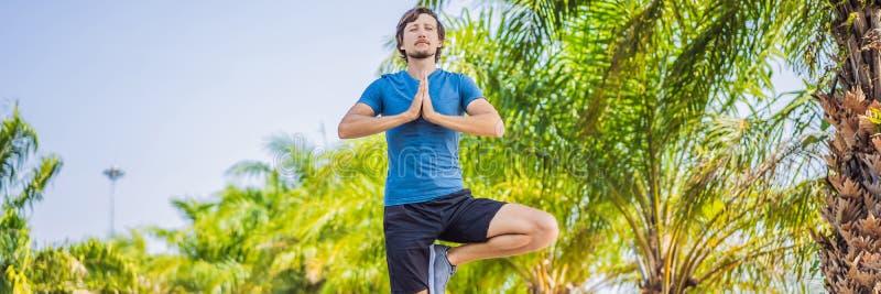 Mannen som gör yoga i ett tropiskt, parkerar BANRET, LÅNGT FORMAT arkivfoton