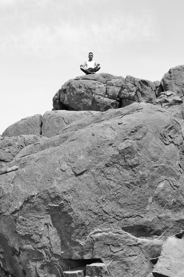 Mannen som gör yogakoncentration på en hög av, vaggar arkivfoton