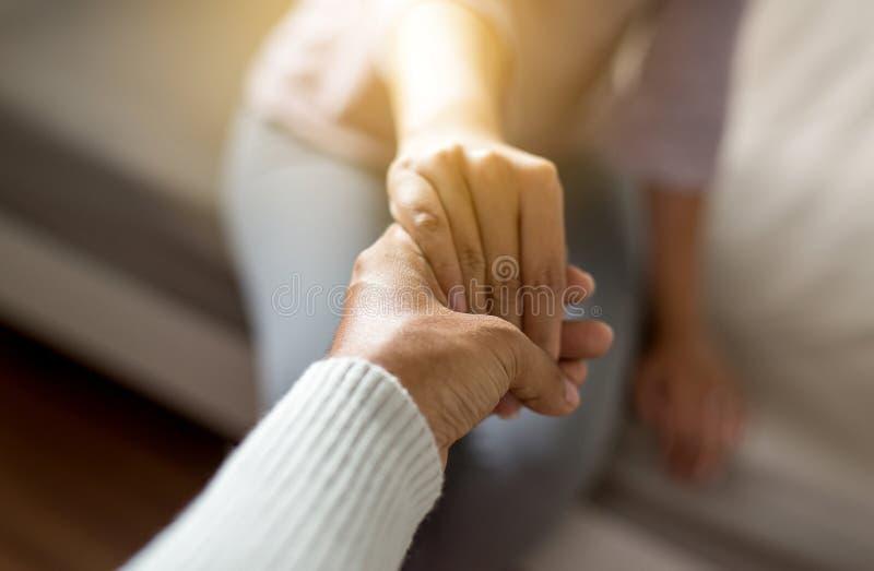 Mannen som ger handen till den deprimerade kvinnan, psykiaterinnehav, räcker patienten, Meantal hälsovårdbegrepp arkivbild