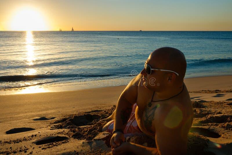 Mannen som håller ögonen på solnedgången i sanden av Barbados, sätter på land royaltyfri bild