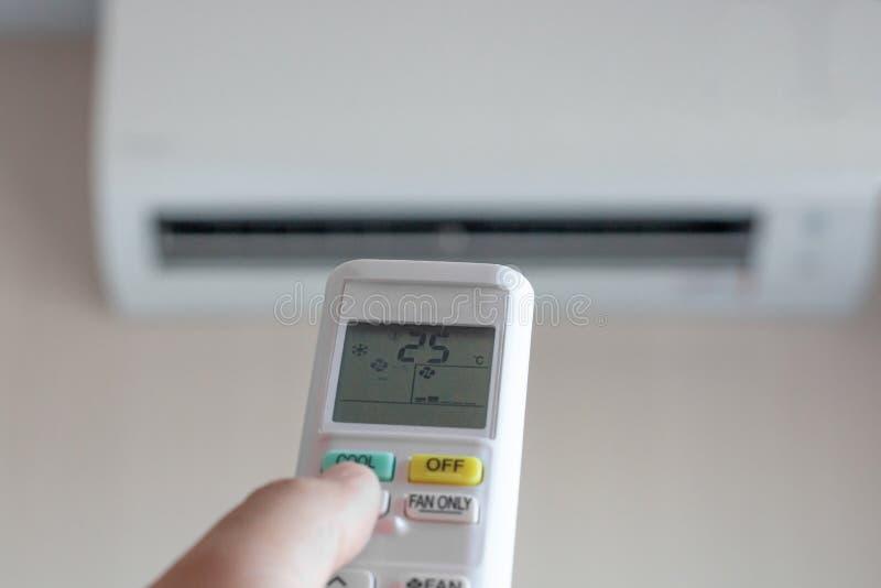Mannen som handen som använder fjärrkontroll, öppnar luftkonditioneringsapparaten, är kall till 25 grader royaltyfria bilder