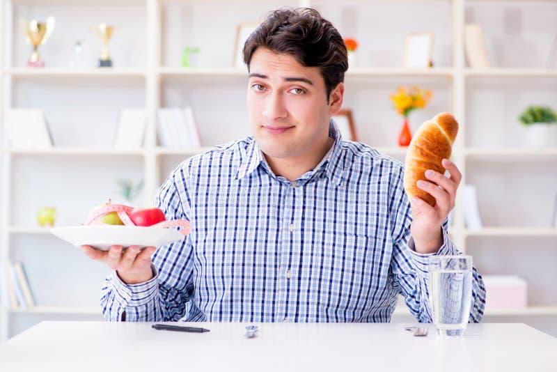 Mannen som har dilemma mellan sund mat och bröd, i att banta, lurar arkivbild